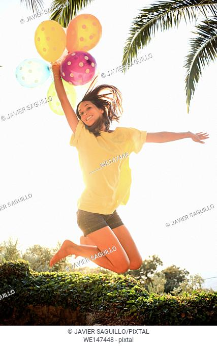 Young woman jumping with balloon