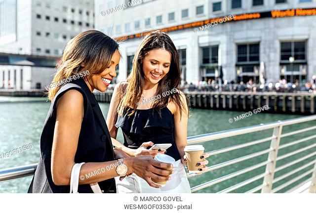 Two women on a bridge with takeaway coffee and cell phone