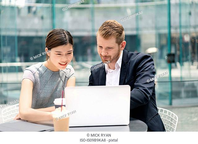 Young businessman and woman looking at laptop at sidewalk cafe meeting