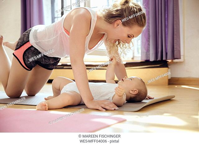 Mother playing with her baby on yoga mat while working out