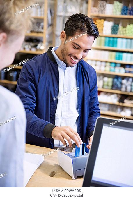 Smiling male shopper using credit card machine at checkout counter in shop