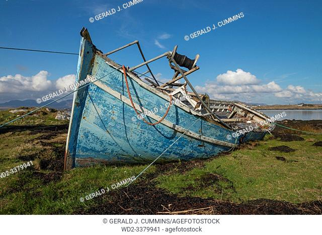 Ireland, Galway, 2016/04 , A blue derelict wooden fishing boat lies decaying on the shoreline of the Irish coast