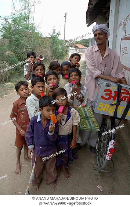 School going children eating red color ice cream , Village Manghawa , District Narsinghpur , Madhya Pradesh , India