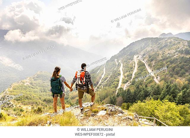 Italy, Massa, couple looking at the beautiful view in the Alpi Apuane