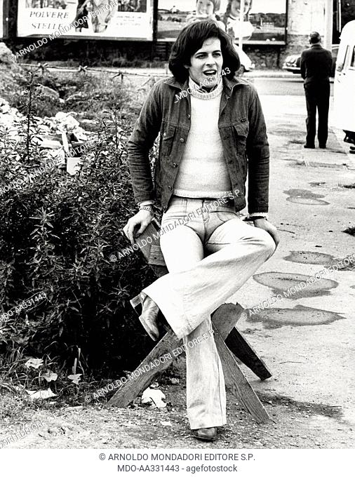 Claudio Baglioni in the outskirts of Rome. The Italian singer Claudio Baglioni leans on an improvised chair in the outskirts of the city. Rome, 1974