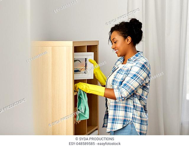 african american woman dusting and cleaning home