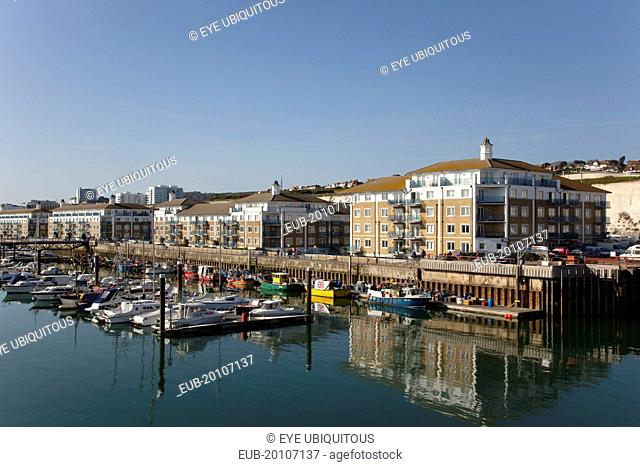 View over boats moored in the Marina with apartment buildings behind