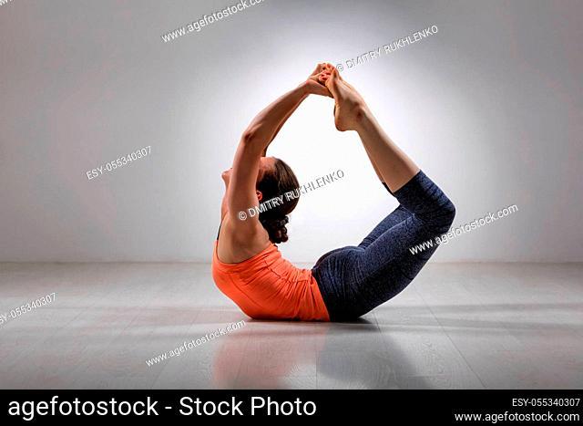 Sporty fit woman practices yoga asana Dhanurasana - bow pose