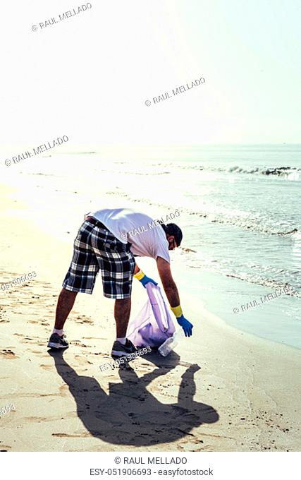 man collecting waste that pollute the sea in plastic bag, people helping to keep nature clean and picking up the garbage from shore