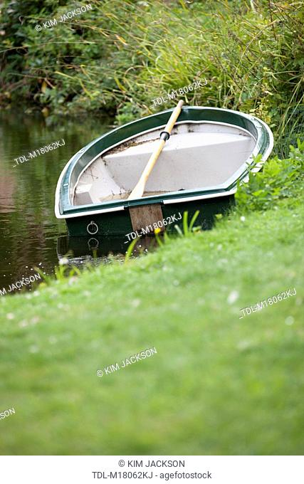 A rowing boat moored on a riverbank