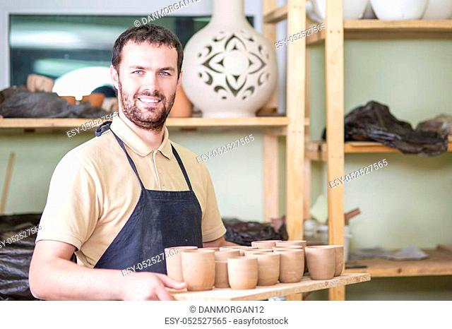 Portrait of Professional Male Ceramist Holding Wooden Tray with Clay Handmade Cups. Posing in Protective Apron in Workshop. Horizontal Shot