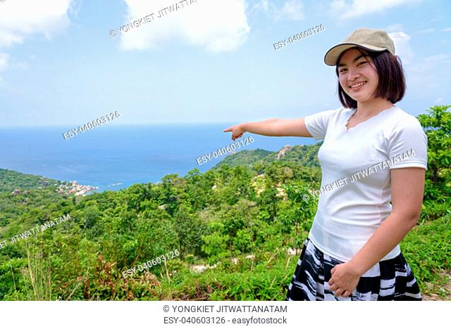 Women tourists raise hand and pointing the finger at the sea on high viewpoint to see the beautiful nature landscape of Koh Tao island is a famous attractions...