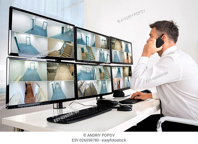 Side view of security system operator using walkie-talkie while looking at CCTV footage