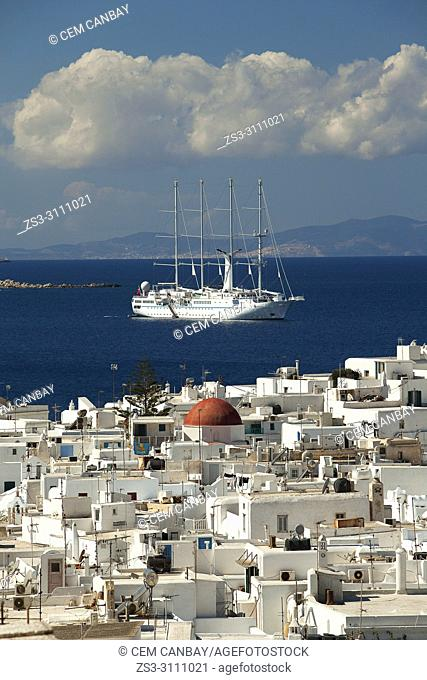View to the whitewashed houses in the town center with a sailing ship in the harbour at the background, Mykonos, Cyclades Islands, Greek Islands, Greece, Europe