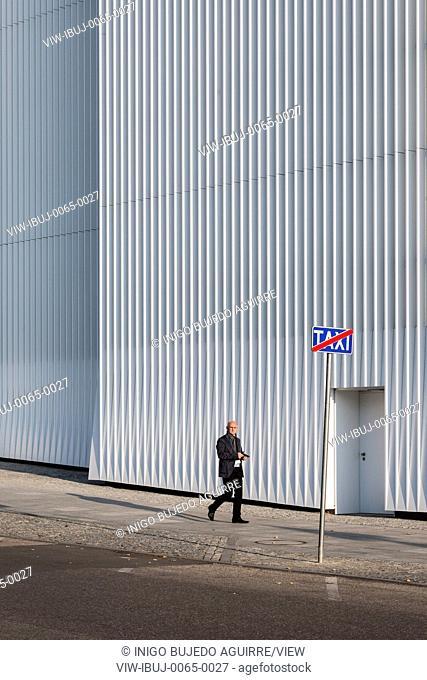 Facade with walkway and passerby. Szczecin Philharmonic Hall, Szczecin, Poland. Architect: Estudio Barozzi Veiga, 2014