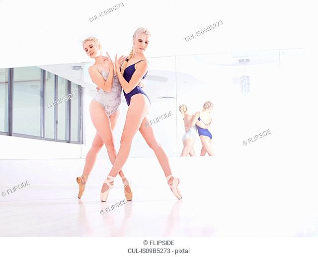 Two female ballet dancers dancing en pointe in dance studio