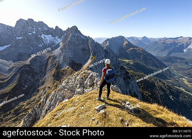 Young woman, mountaineer with climbing helmet looking at mountain landscape, hike to Ehrwalder Sonnenspitze, behind Grünstein and western Marienbergspitze