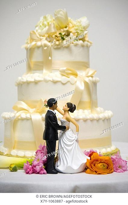Dolls representing a bride and a groom stand in front of a wedding cake