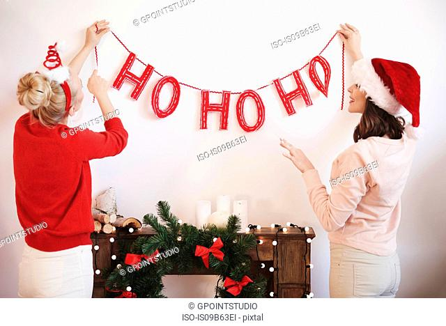 Rear view of two young women putting up christmas decorations on wall