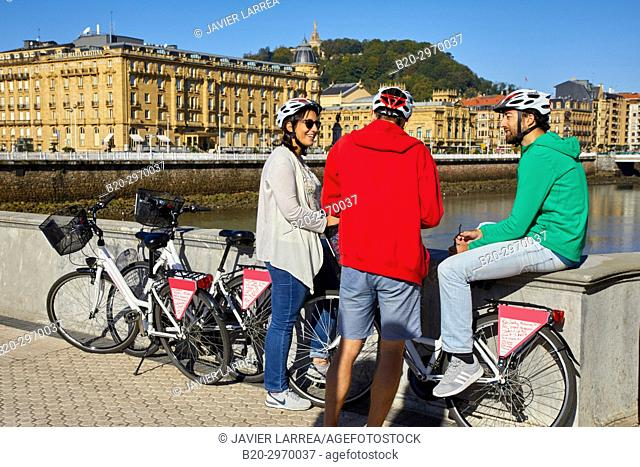 Group of tourists and guide making a bicycle tour through the city, Maria Cristina Hotel, Victoria Eugenia Theatre, Urumea river, Donostia, San Sebastian