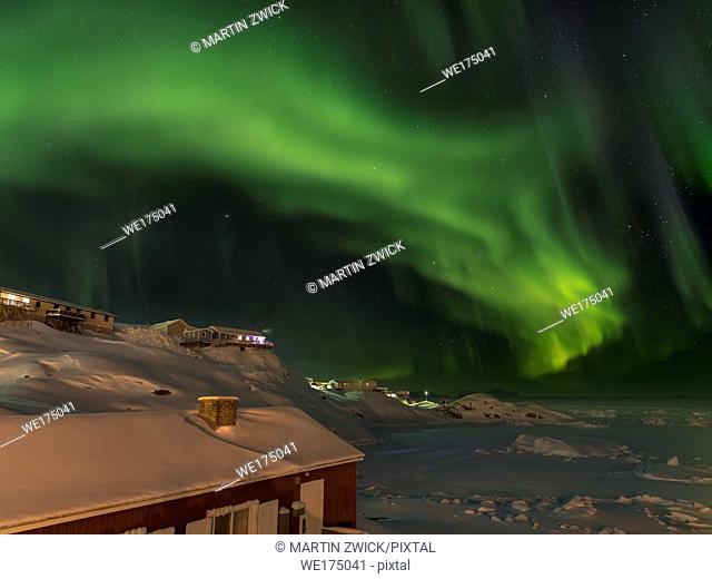 Northern Lights over town and frozen Disko Bay. Town Ilulissat at the shore of Disko Bay in West Greenland, center for tourism, administration and economy