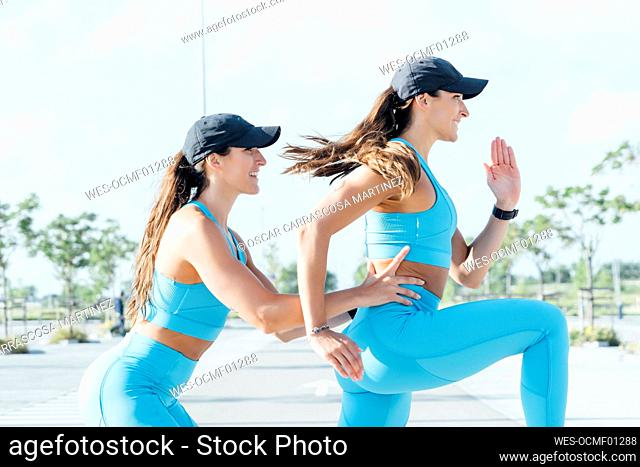 Young woman assisting twin sister exercising on sunny day