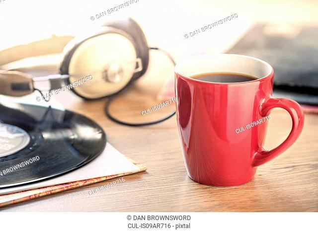 Still life of black coffee, headphones and vinyl record