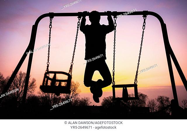 Male jogger warming up doing pull ups on swing frame at sunrise in public park on a frosty morning. Billingham, England, United Kingdom