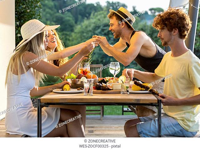 Happy friends having dinner at outdoor table