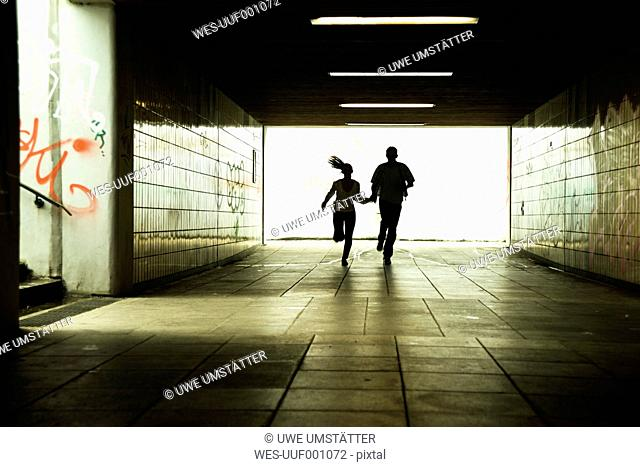 Young couple running together in a dark underpass