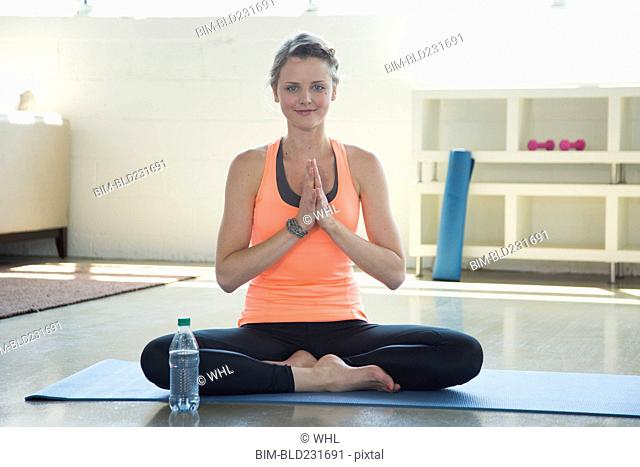 Caucasian woman doing yoga with hands clasped
