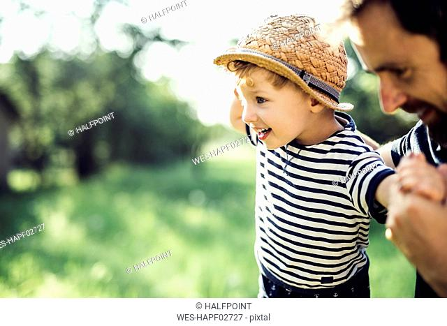 Father assisting little boy in balancing outdoors