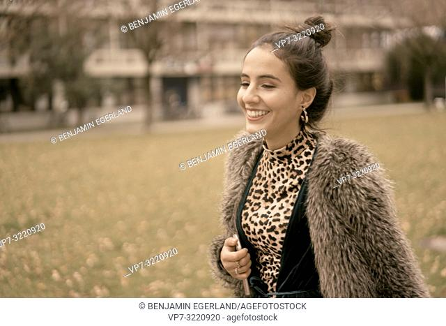fashionable vibrant woman running outdoors in park, closed eyes, autumn season, wearing coat, happy laughing, candid emotion, walking in city, Munich, Germany