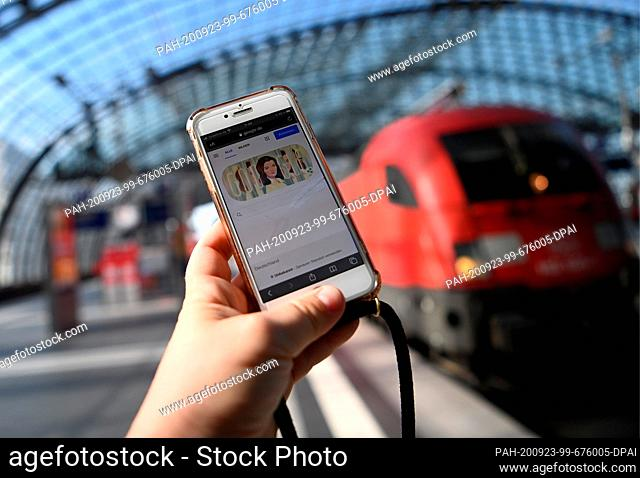 23 September 2020, Berlin: A woman is holding a mobile phone in her hand at Berlin Central Station. Rail customers and visitors can now dial into a new Deutsche...