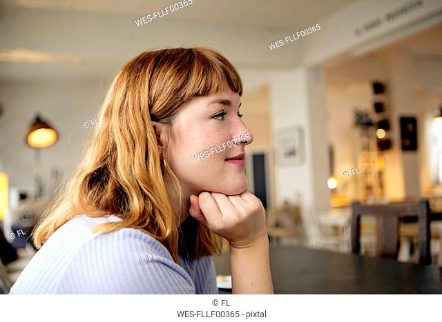 Portrait of strawberry blonde young woman with nose piercing in a cafe