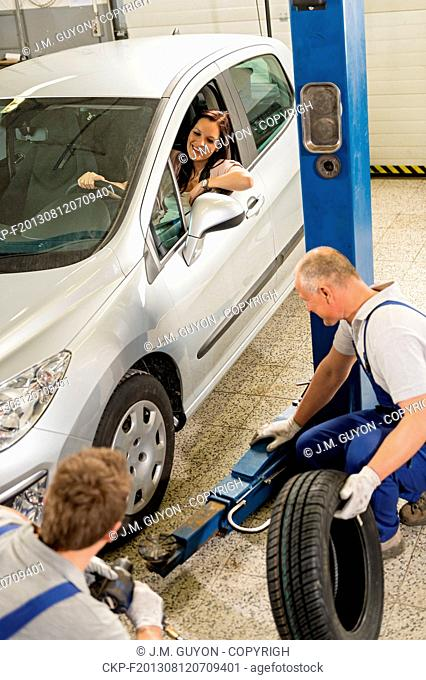 Caucasian car salesman changing tire in garage