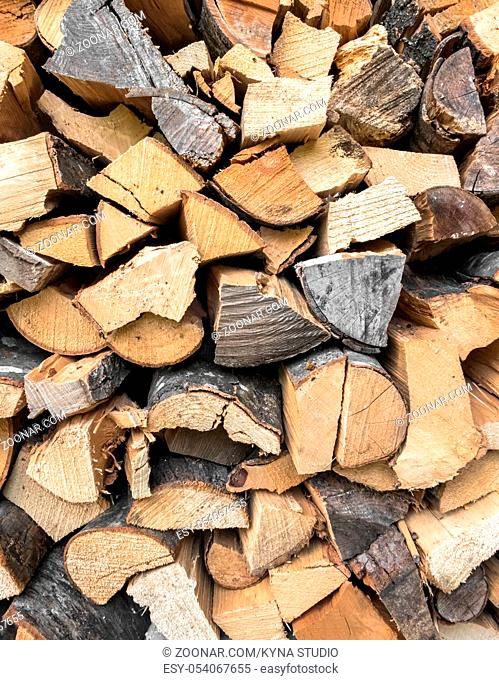 Background of dry chopped firewood. Stock pyre dry for fuel. They use for cook and make heat when cold weather