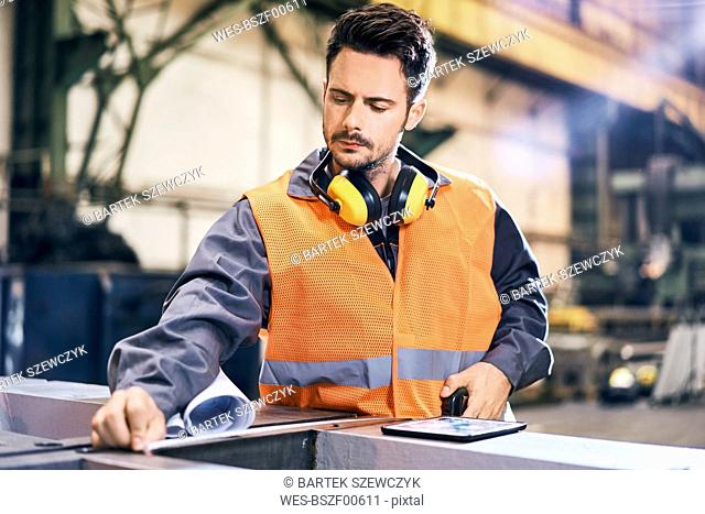 Man wearing protective workwear working in factory