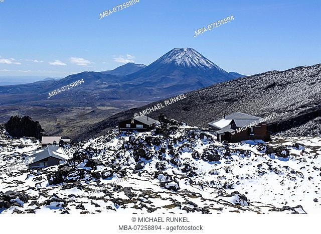 View from Mount Ruapehu on Mount Ngauruhoe with a ski cottage in the foreground. Unesco world heritage sight Tongariro National Park, North Island, New Zealand