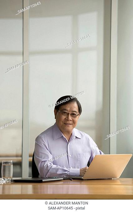 Singapore, Senior businessman using laptop at desk