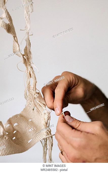 An artist working on an art piece, creating an object with thread