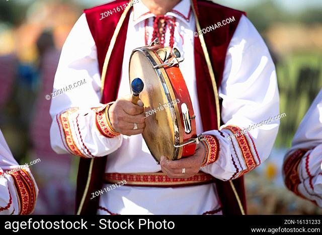 A musician in embroidery plays an ethnic drum