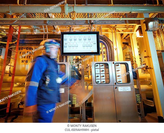 Engineer passing digital display in power station
