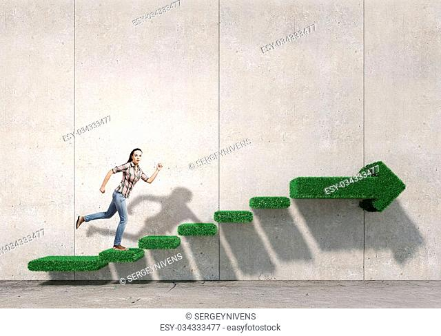 Young woman running on green grass staircase