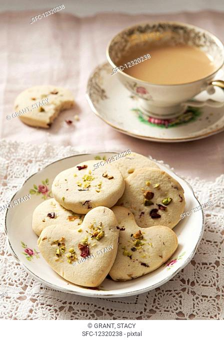 Cookies with pistachios and dried rose petals, served with a cup of coffee