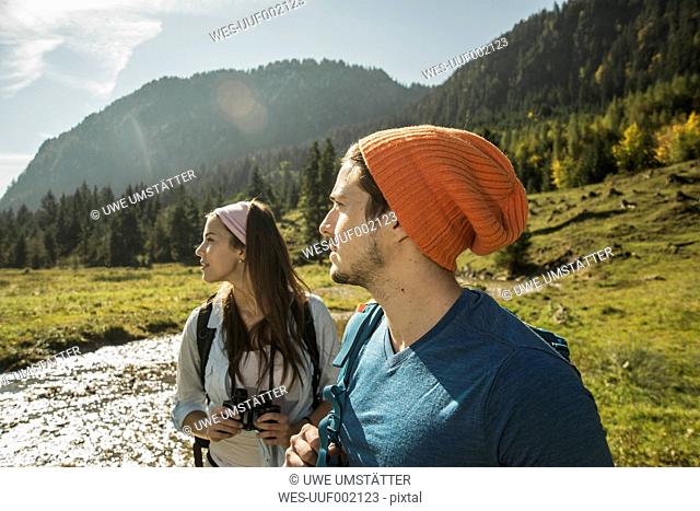 Austria, Tyrol, Tannheimer Tal, two young hikers watching landscape