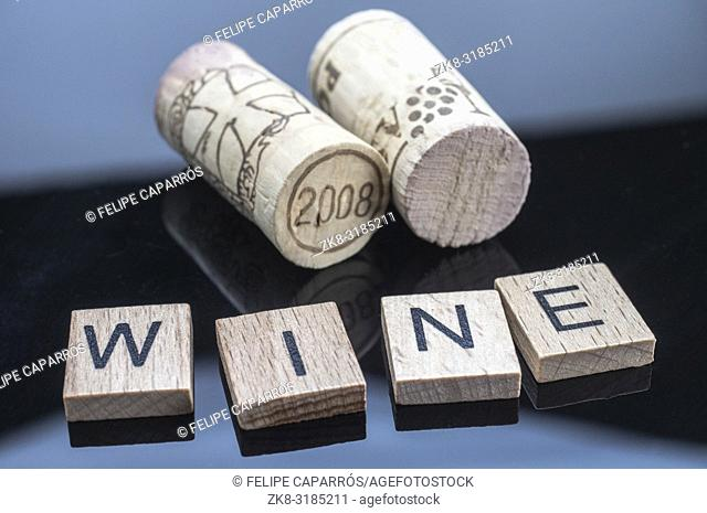 Two corks next to a few letters of wood with the word wine