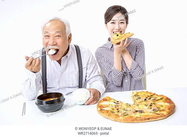 Smiling senior man eating rice and smiling young woman eating pizza