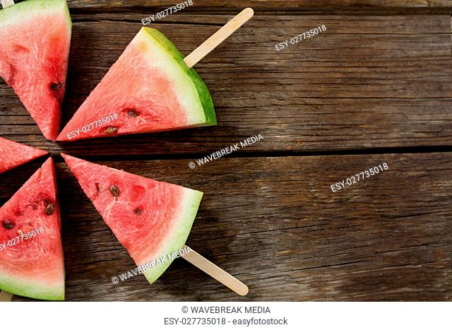 Slices of watermelon arranged on wooden table