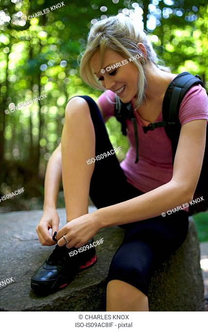 Woman sitting on rock in forest tying shoelaces